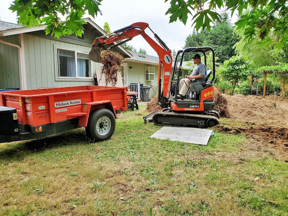 Loading stumps into dump trailer.